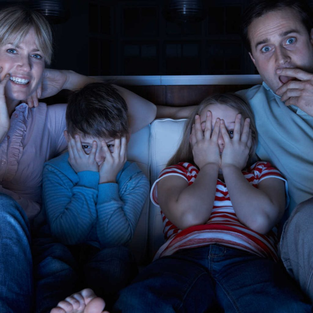 family sitting on couch for movie night two kids in the middle with their hands covering their eyes and a woman on the left and a man on the right