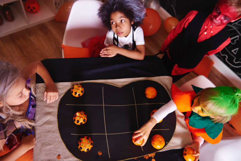 Kids playing tic tac toe with mandarin oranges on a pumpkin board