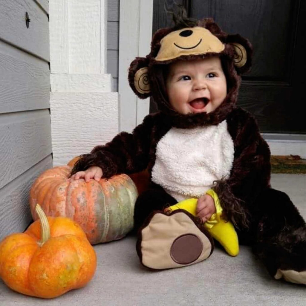 baby sitting on porch in brown bear costume. 2 pumpkins next to baby
