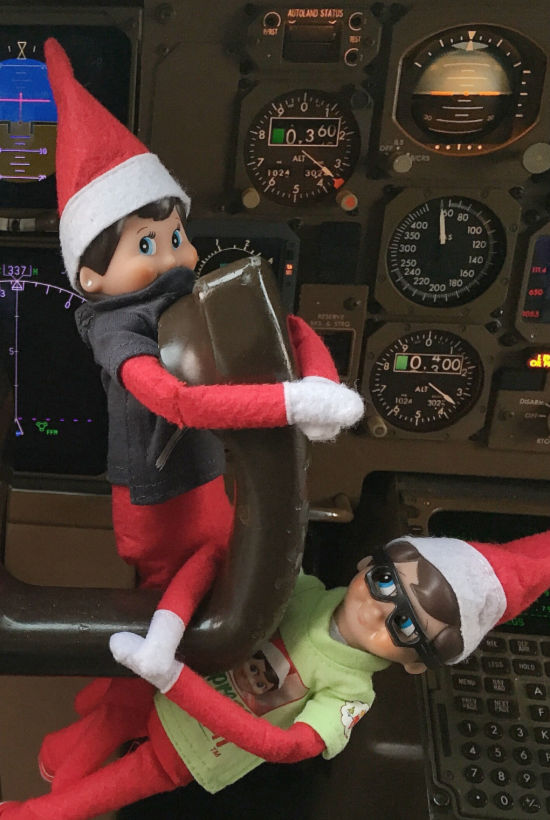 two boy elf on the shelves holding a cockpit handle. one in green shirt with sunglasses on. Other elf has a black shirt on