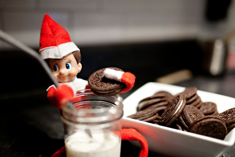 Red boy elf holding oreo and straw with cup of milk in front of him.  Bowl of oreos behind him.