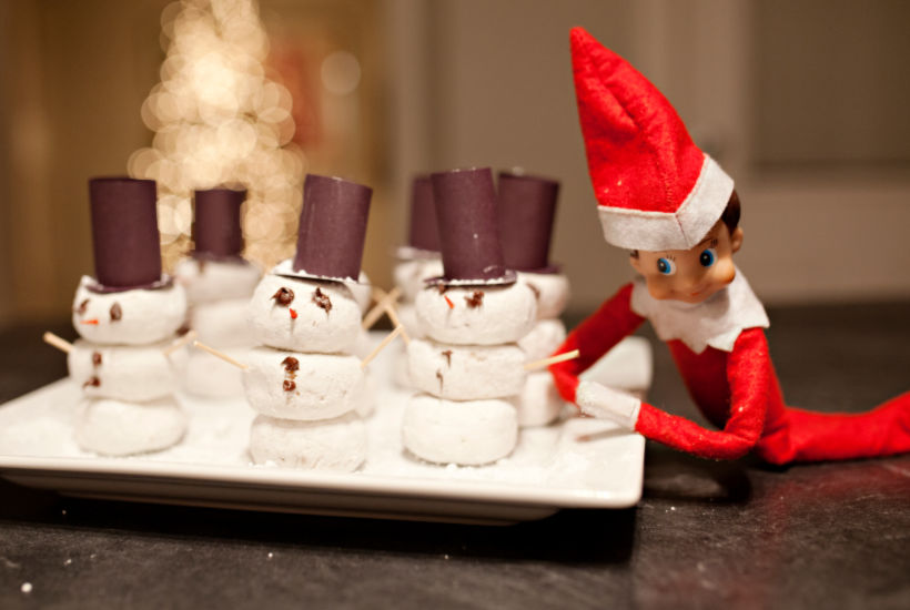Red elf on the shelf leaning on white plate of powdered snowmen with top hats