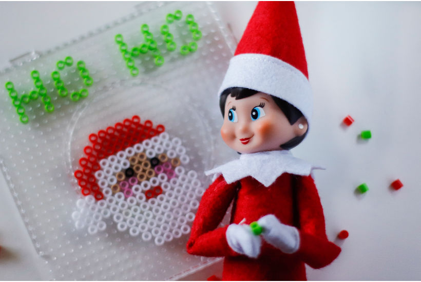 female elf creating image of Santa with perler beads with ho ho on top.