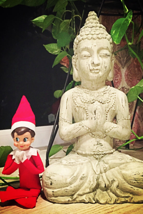 Elf with statue both in Namaste post with legs crossed and hands in front of them.
