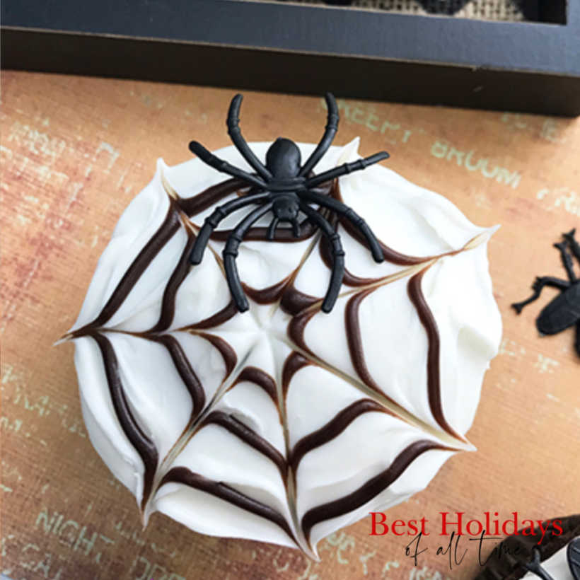 closerup of a white frosted cupcake with a brown spiderweb on top and a fake spider resting on the spiderweb